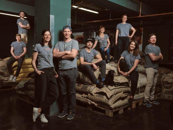 Das gesamte Wildkaffee Team im Rohkaffeelager in unseren Team-Shirts.