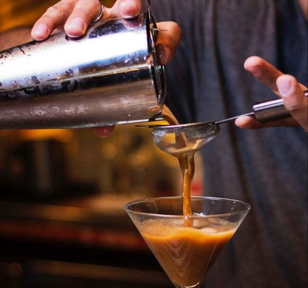 Ein Barista seiht den Kaffee-Cocktail ab.