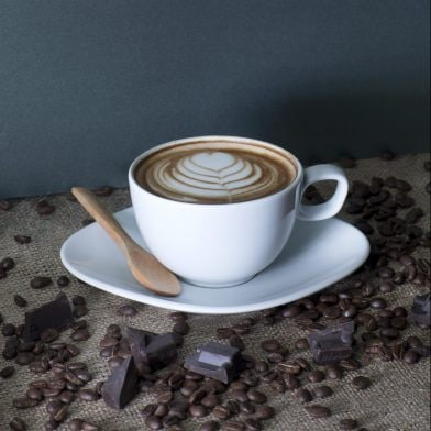 A cup of fresh coffee with a flower formed cream and a wooden spoon on the gunny sack table with coffee beans and chocolate